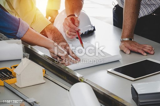 construction worker team planning about building plan with blueprint, safety helmet, construction tools on conference table at construction site, contractor, business, industry, construction concept
