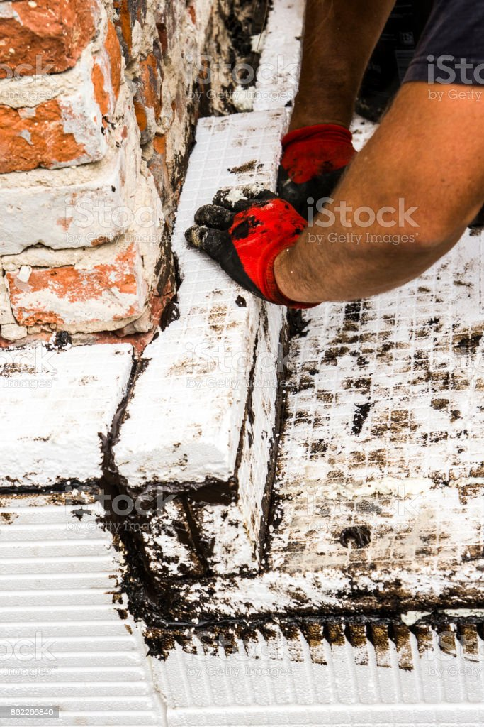 Construction worker thermally insulating house foundation walls with Styrofoam boards stock photo