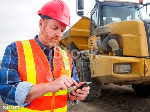 1054724700istockphoto Construction worker, truck, texting and internet and engineer 508058370