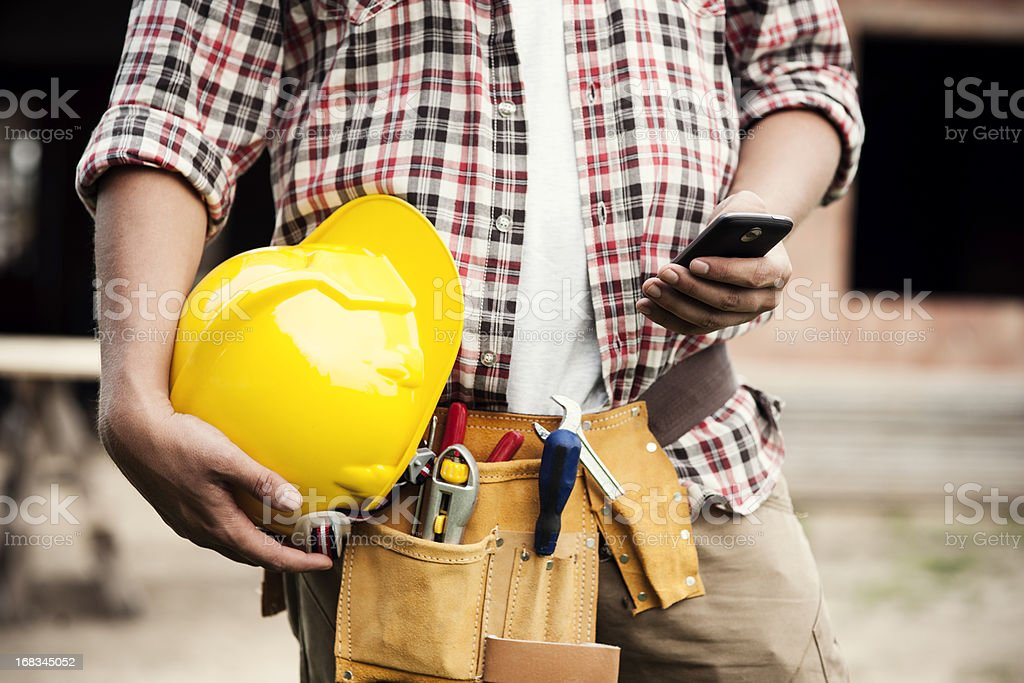 Construction worker typing on a smartphone stock photo