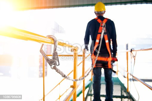 istock Construction worker use safety harness and safety line working on a new construction site project. 1036795608
