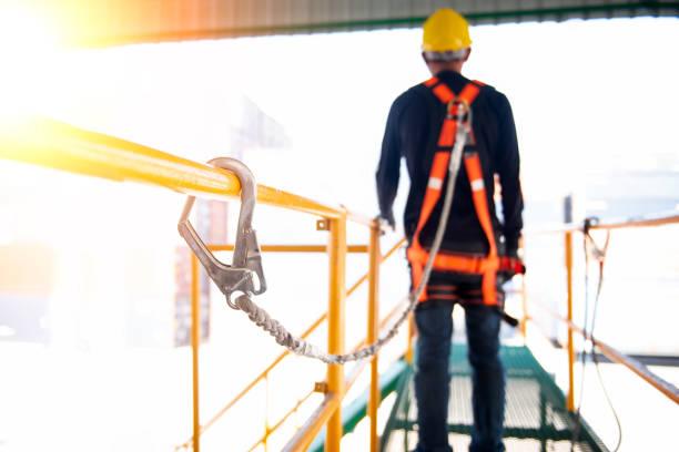 ouvrier du bâtiment utilisent le harnais de sécurité et de la ligne de sécurité travaillant sur un projet de site de construction. - élevé photos et images de collection