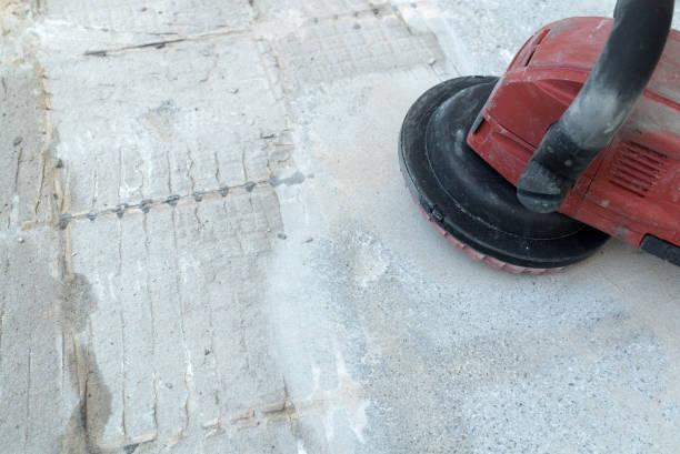 Bauarbeiter verwendet eine Betonschleifmaschine zum Entfernen von Fliesenkleber und Harz während der Renovierungsarbeiten – Foto