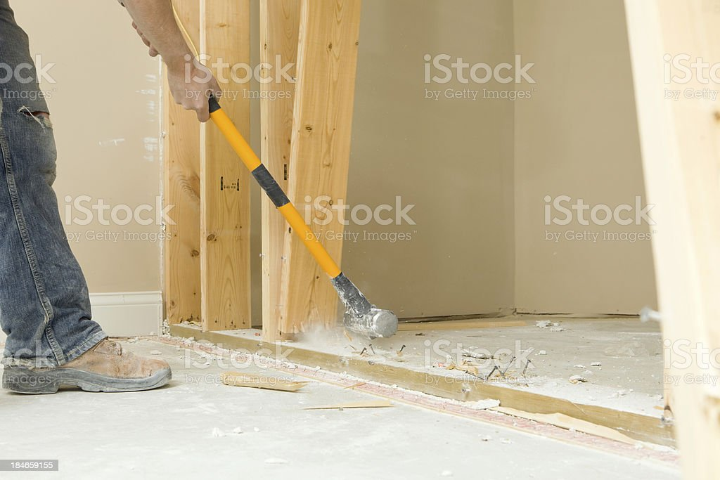 Construction Worker Using a Sledgehammer to Remove Wall Stud stock photo