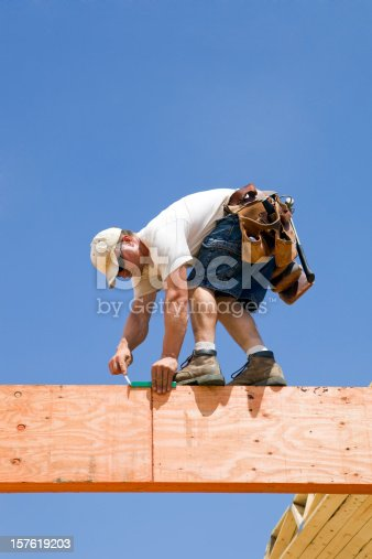 A construction worker is balancing on a laminated structural support beam and using a speed square to mark a measurement  on the second level of a home construction project.