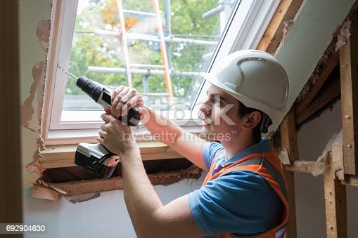 istock Construction Worker Using Drill To Install Replacement Window 692904630