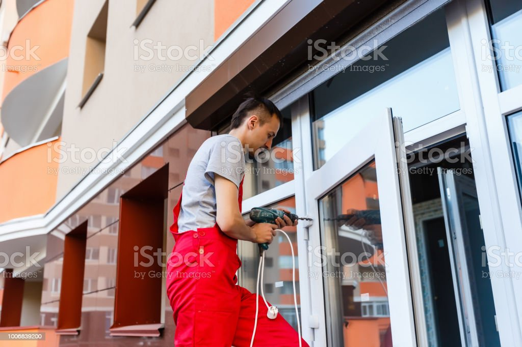 Construction Worker Using Drill To Install Window stock photo