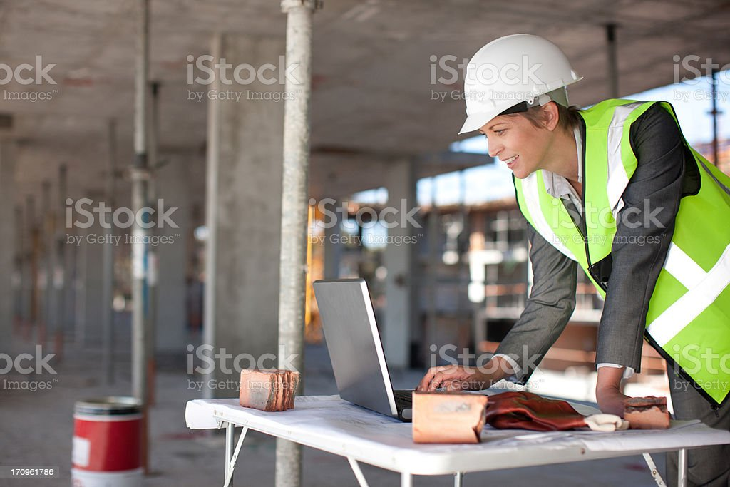 Construction worker using laptop on construction site stock photo