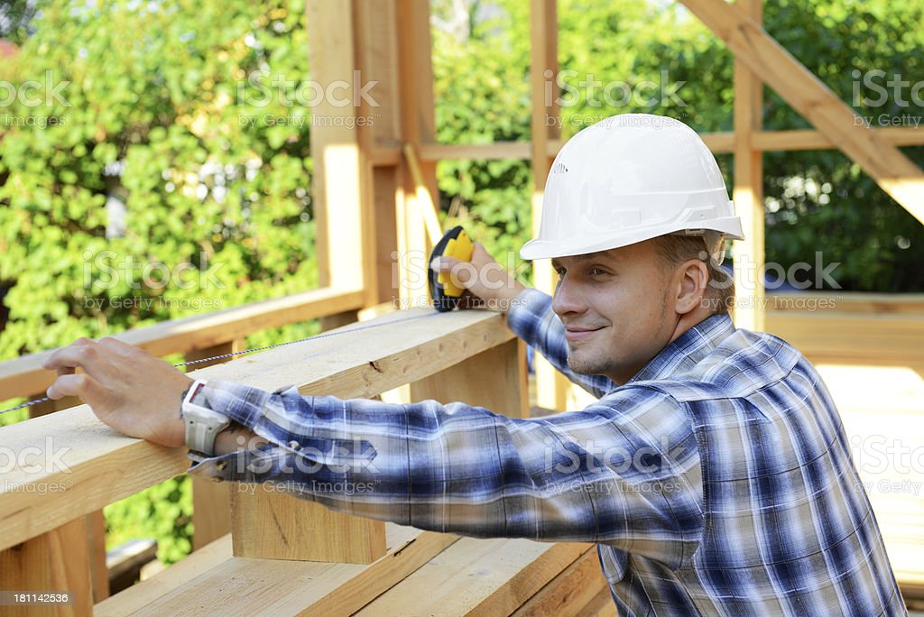 Construction worker using tape measure on frame royalty-free stock photo