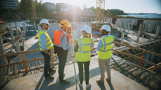 Construction Worker Using Theodolite Surveying Optical Instrument for Measuring Angles in Horizontal and Vertical Planes on Construction Site. Engineers and Architect Discuss Plans Next to Surveyor.
