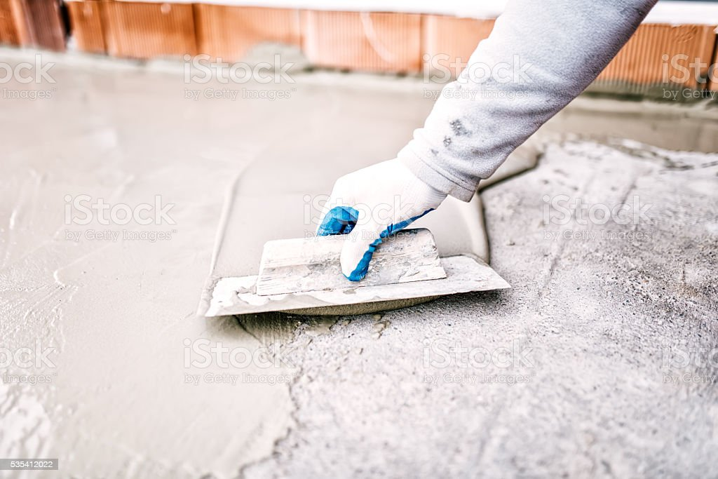 construction worker using trowel and mason's float for waterproofing house stock photo
