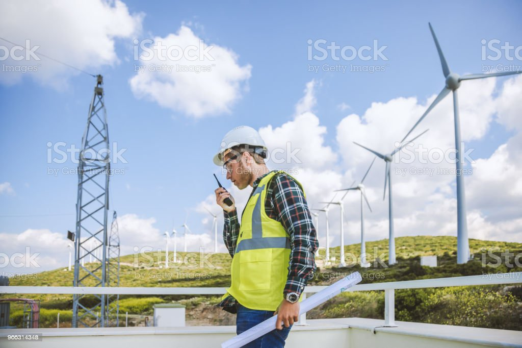 Construction worker using walkie-talkie against power plant stock photo