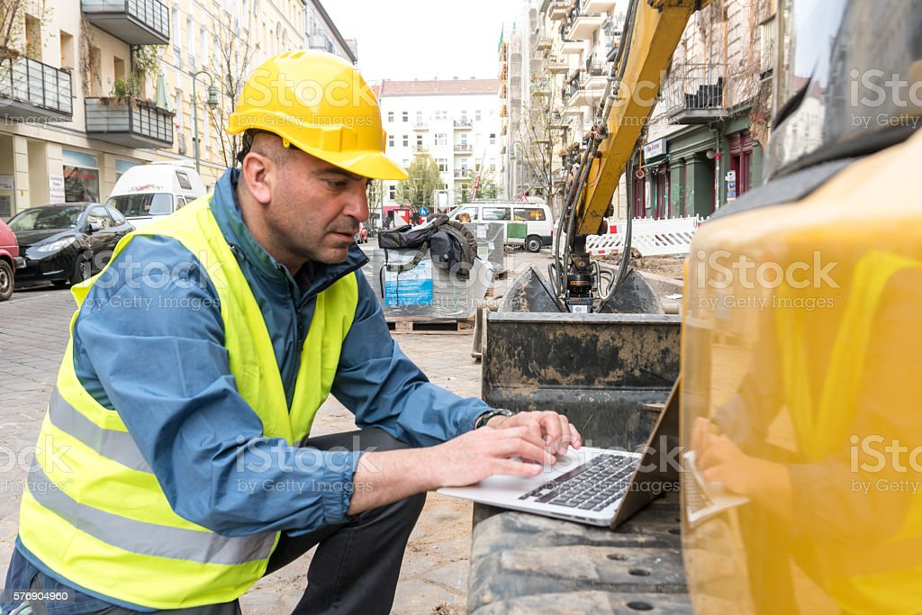 Construction worker wearing safety equipment working at computer – Foto