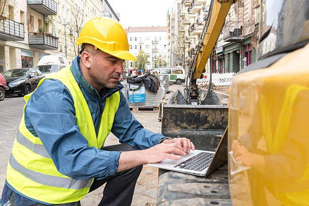Construction worker wearing safety equipment working at computer stock photo
