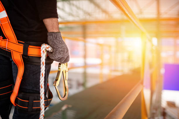 Construction worker wearing safety harness and safety line Construction worker wearing safety harness and safety line working at high place high up stock pictures, royalty-free photos & images