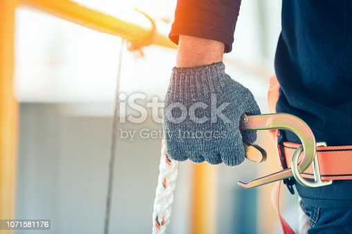 istock Construction worker wearing safety harness and safety line working at high place 1071581176