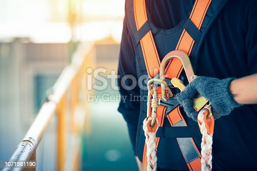 istock Construction worker wearing safety harness and safety line working at high place 1071581190