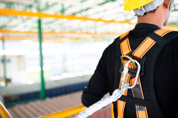 Construction worker wearing safety harness and safety line working on construction Construction worker wearing safety harness and safety line working on construction safety harness stock pictures, royalty-free photos & images
