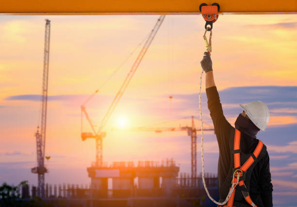 Construction worker wearing safety harness. Construction worker wearing safety harness and safety line working high place at industrial. safety harness stock pictures, royalty-free photos & images