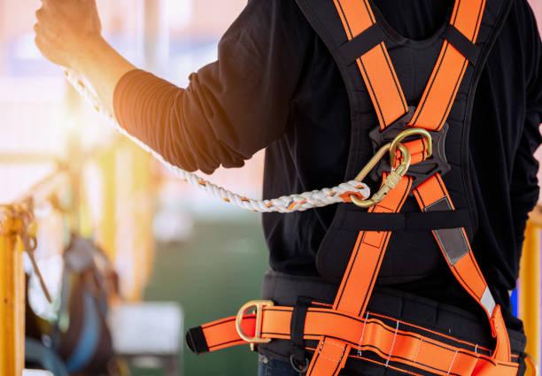 operaio edile che indossa un'imbracatura di sicurezza. - protezione foto e immagini stock