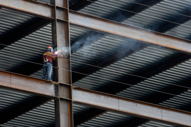 Construction Worker Welding Beam on High Rise Building  girder stock pictures, royalty-free photos & images