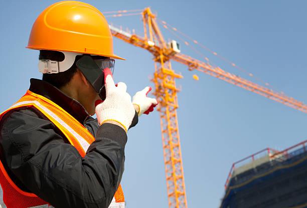 Bauarbeiter mit Kran im Hintergrund – Foto