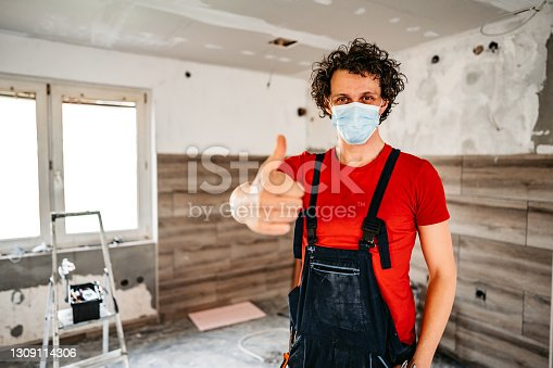 Portrait of young handsome construction worker with protective face mask renovating apartment.