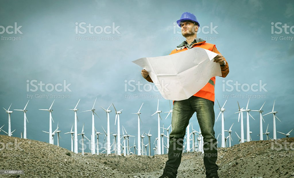 Construction worker with plans at wind farm stock photo