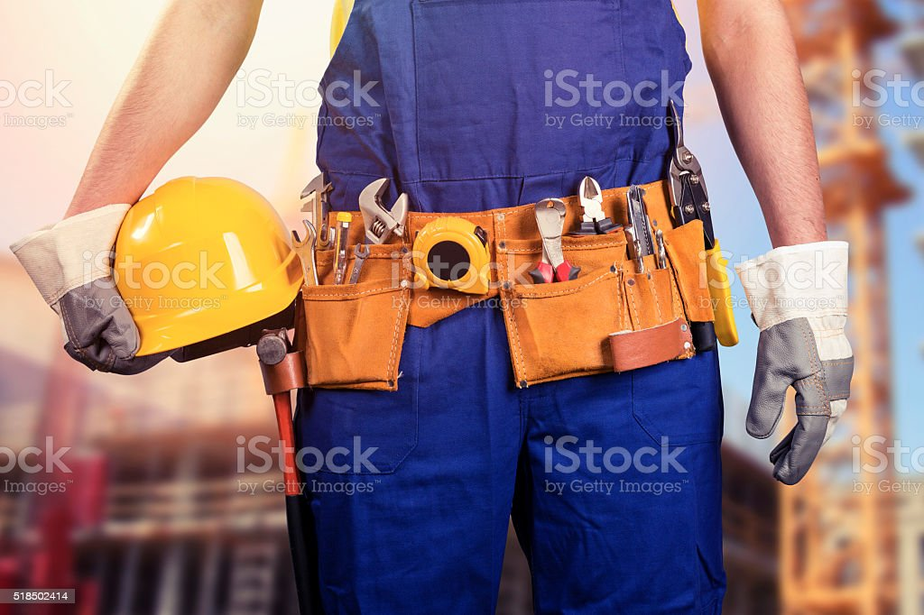 construction worker with tool belt at building site stock photo