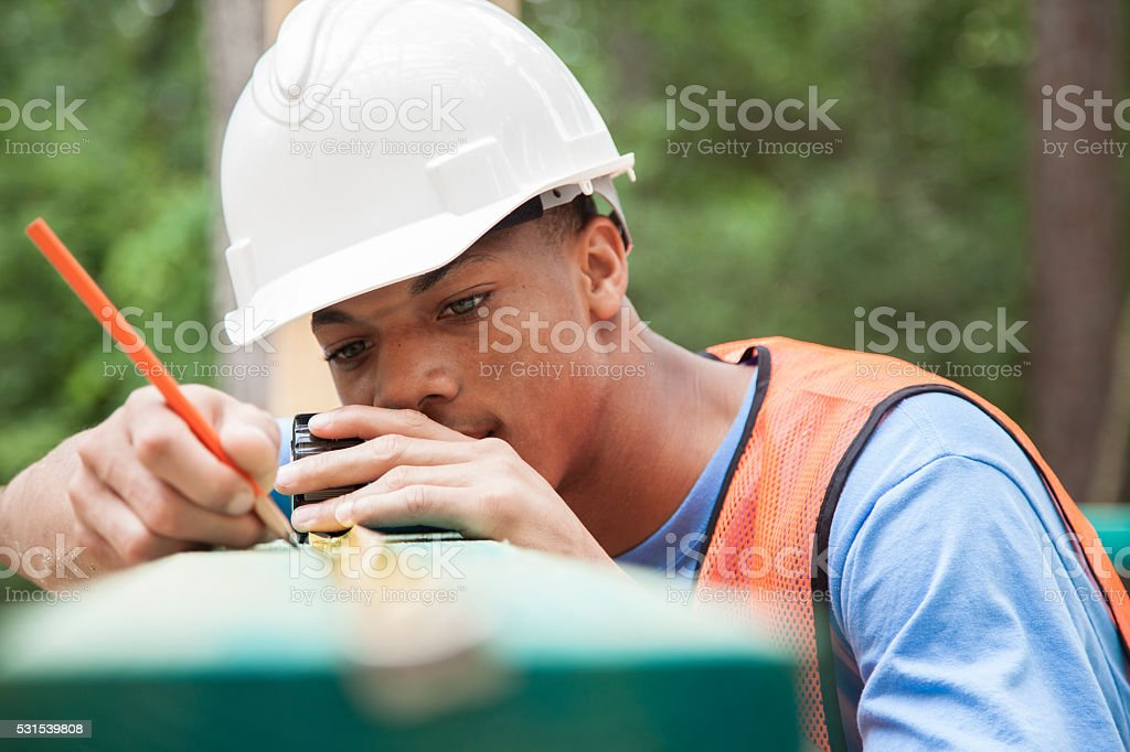 Construction worker working at job site.  Measuring board. stock photo