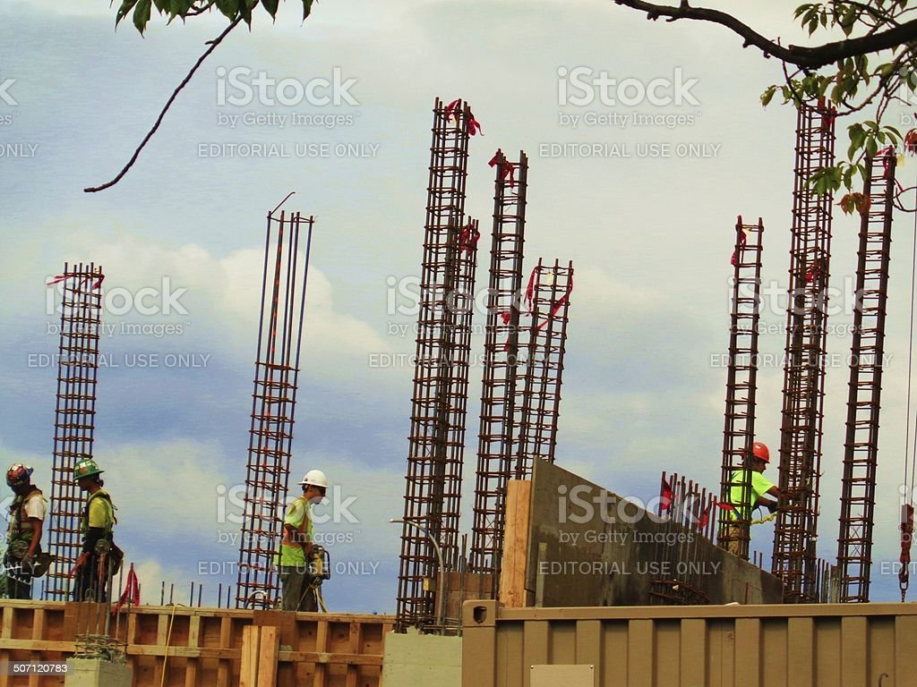 Construction workers among towers of rebar stock photo