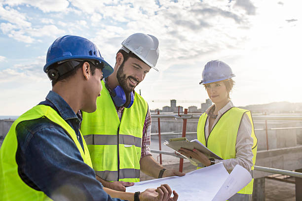 Construction workers and architect looking at blueprints on construction site stock photo