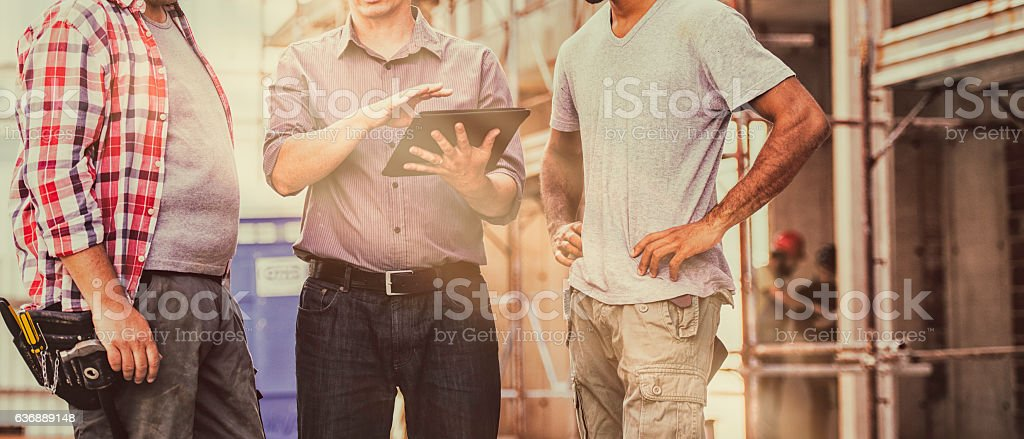 Construction workers and architect with digital tablet stock photo