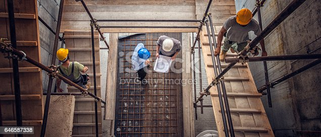 istock Construction workers and architects viewed from above 646587338
