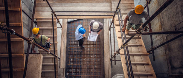 construction workers and architects viewed from above - ingegneria foto e immagini stock