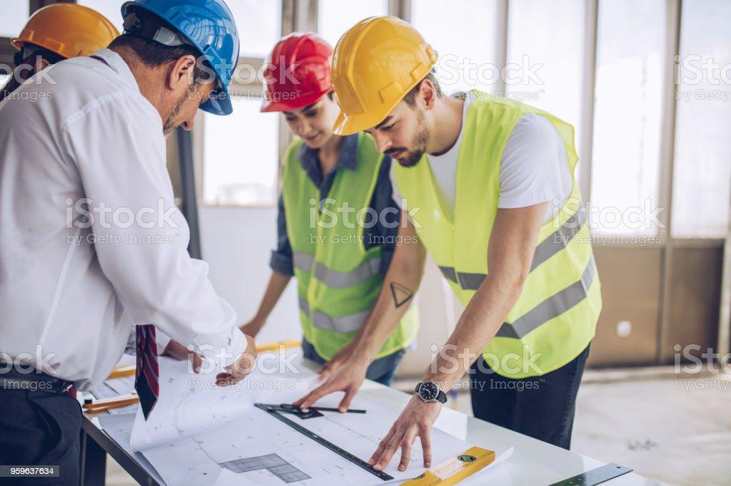 Trabajadores de la construcción y arquitectos trabajando en obra - Foto de stock de Accesorio de cabeza libre de derechos