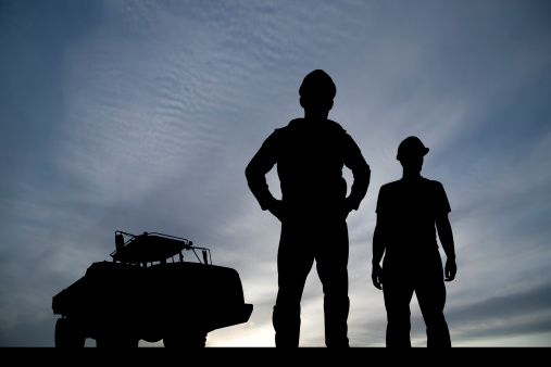Two construction workers stand with a dump truck off in the distance.
