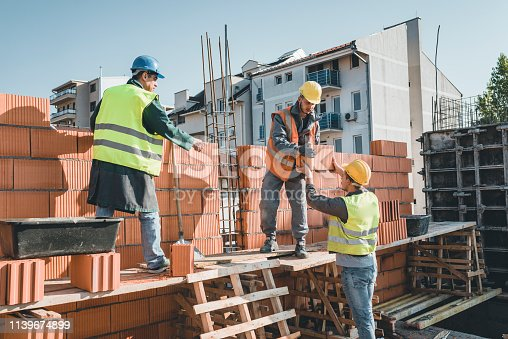 Young Building Workers is Helping out his Experienced Colleague at the Roof of the Construction Site. Teamwork by Three Builders with Protective Helmets who are Building a Wall of Bricks at the Building Site.