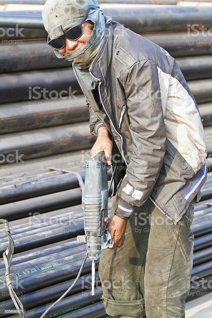 Construction workers are using the drill floor penetrate mortar stock photo