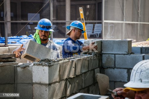 Construction workers at a job site in SW Florida are building a concrete block wall.