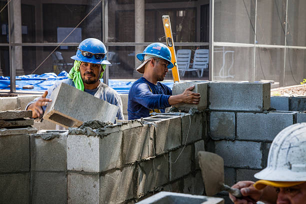Construction Workers Building Concrete Block Wall stock photo