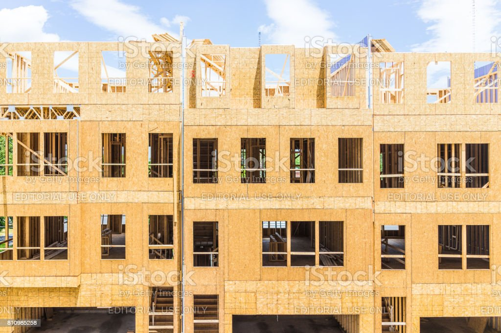 Construction workers building new modern townhouses with garages on...