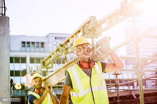 Male construction workers in protective workwear carrying plank at site