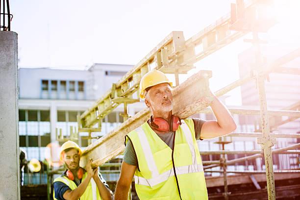 construction workers carrying plank at site - kask ochronny odzież ochronna zdjęcia i obrazy z banku zdjęć