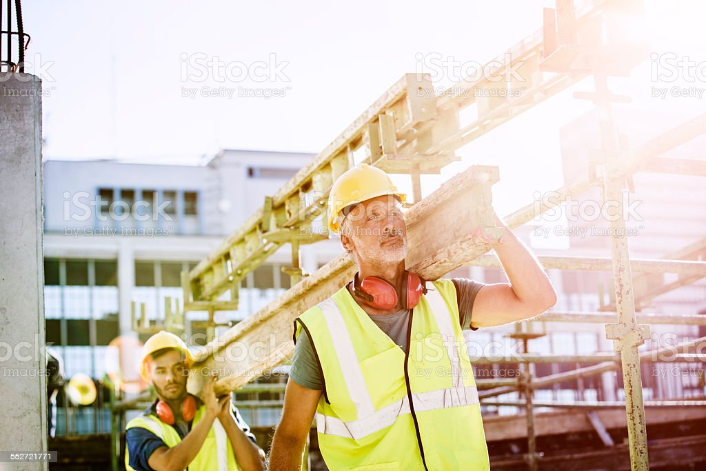 Construction workers carrying plank at site stock photo