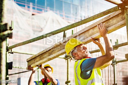 Male construction workers in carrying plank at site