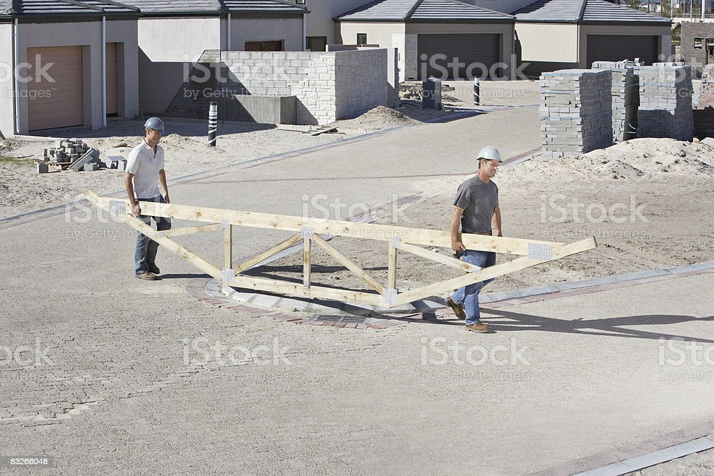 Construction workers carrying roof truss at construction site royalty free stockfoto