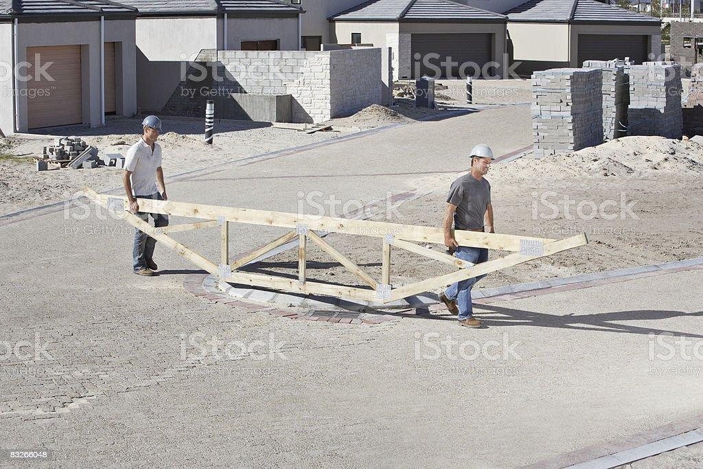 Operai edili trasporto capriate del tetto in Cantiere di costruzione foto stock royalty-free