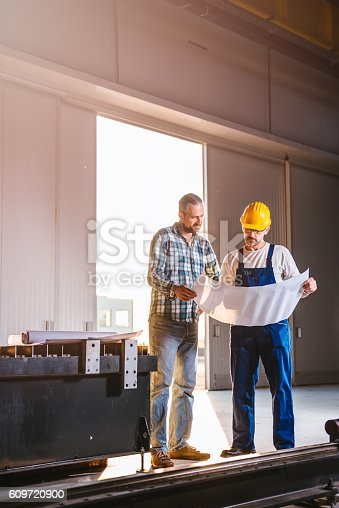 istock Construction workers checking checking blue print 609720900