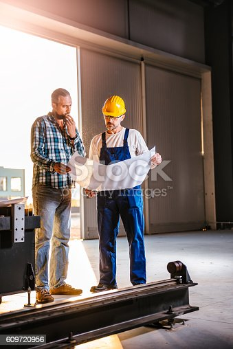 istock Construction workers checking checking blue print 609720956